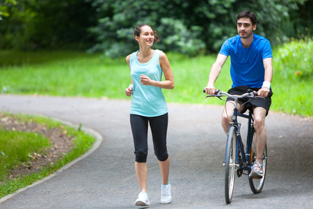 View of a Young sportive couple jogging at the park