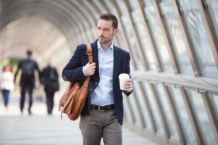 View of a Young attractive man drinking coffee on his way photo