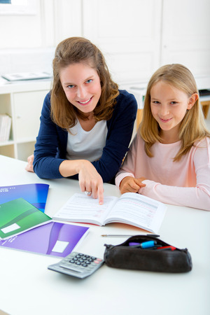 pedagogic: View of a Woman helping out her little sister for homework