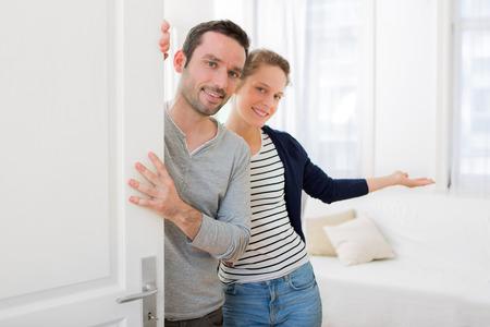 puertas abiertas: Vista de una pareja joven y atractiva darle la bienvenida en su casa Foto de archivo