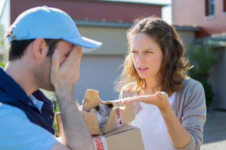 View of a Young attractive woman angry against delivery man Stock Photo