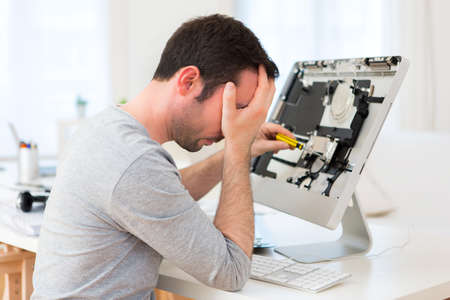 computer repairing: View of a Young attractive man trying to repair computer