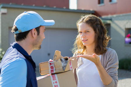 unprofessional: View of a Young attractive woman angry against delivery man Stock Photo