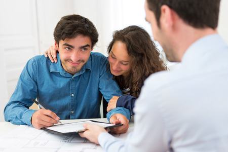 View of a Young attractive couple signing contract photo