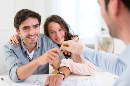 View of a Real estate handing over keys to couple photo