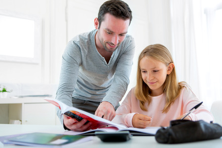 pedagogic: View of a Father helping out her daughter for homework