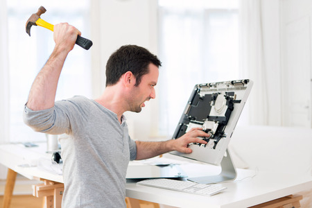 computer memory: View of a Young attractive man angry against computer Stock Photo