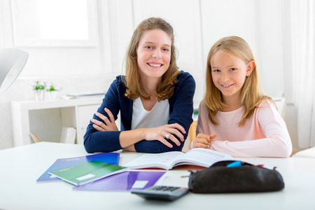 pedagogic: Portrait of a Woman helping out her little sister for homework