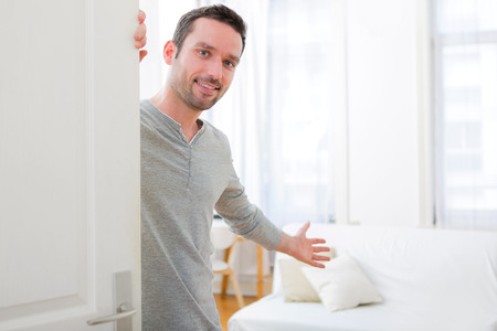 View of a Young attractive man welcoming you in his house Standard-Bild