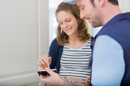 house exchange: View of a Young attractive woman signing on delivery paper