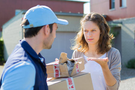 embarassed: View of a Young attractive woman angry against delivery man Stock Photo