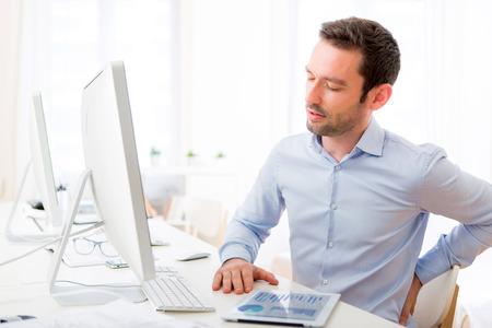 dolor de espalda: Vista de un hombre atractivo joven tiene un dolor de espalda en la oficina