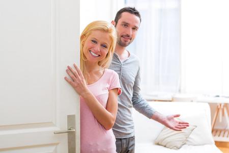 Weergave van een jonge aantrekkelijke paar u te mogen verwelkomen in zijn huis