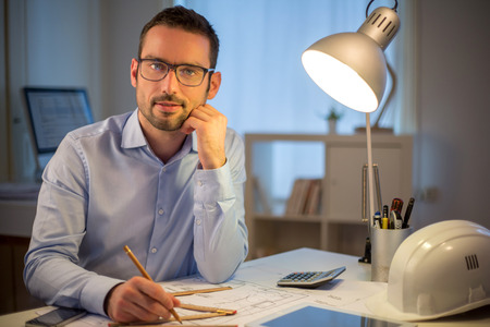 late thirties: View of a Young attractive architect working late at office