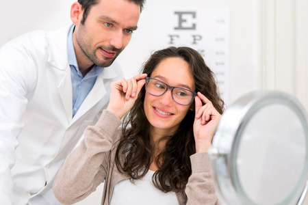 View of a Optician helping out a woman to choose glasses Banco de Imagens