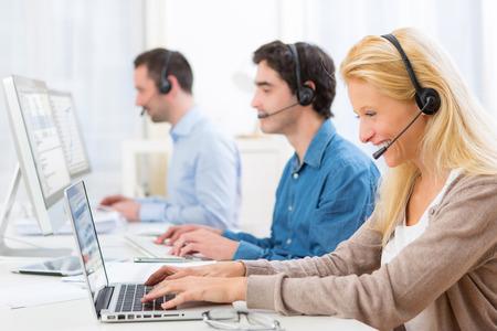 computer centre: Vista de una mujer atractiva joven que trabaja en un centro de llamadas