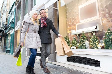 ショッピング バッグと若い魅力的なカップルのビュー 写真素材