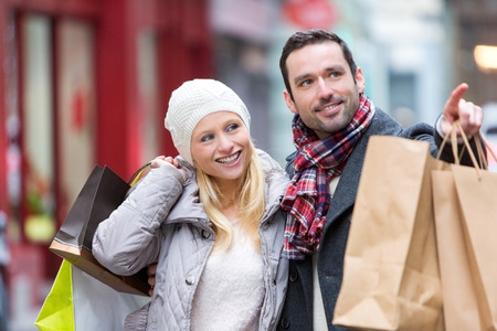 winter woman: View of a Young attractive couple with shopping bags Stock Photo