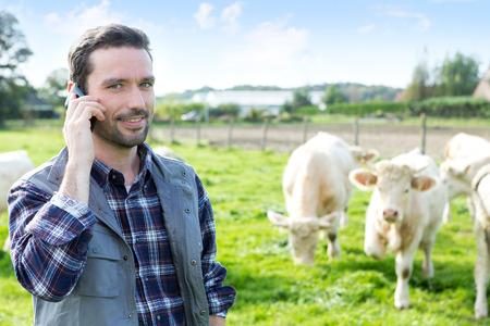 granjero: Vista de un agricultor atractiva joven que usa el tel�fono m�vil en un campo Foto de archivo