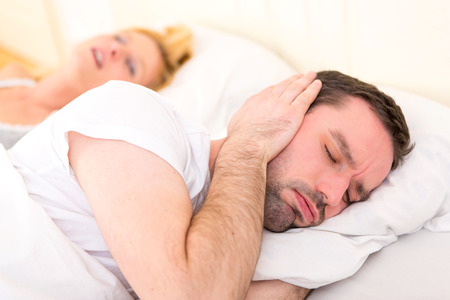 snoring: View of a Young man cant sleep because of girlfriends snoring