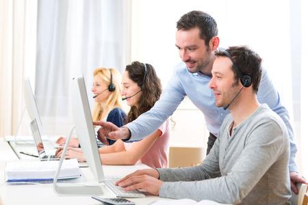 Vue d'un gestionnaire de la formation d'un des jeunes attrayants sur l'ordinateur Banque d'images