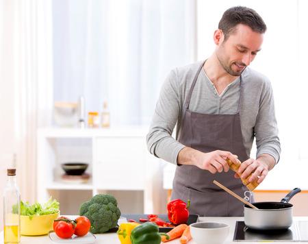 キッチンで料理をして若い魅力的な人間観