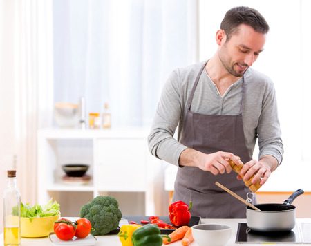 View of a Young attractive man cooking in a kitchen Stockfoto
