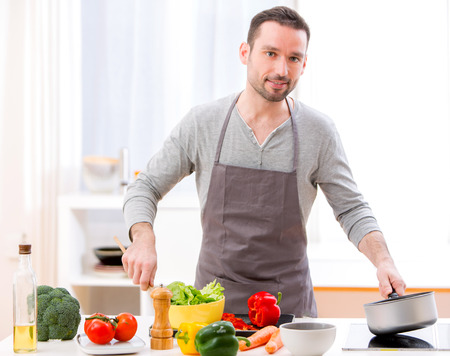 View of a Young attractive man cooking in a kitchen Stock Photo