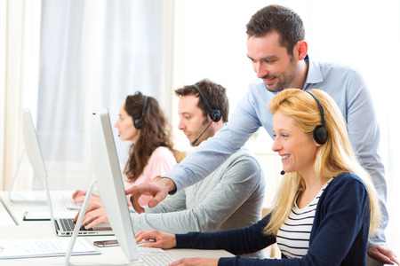 View of a Manager training a young attractive people on computer Stock Photo
