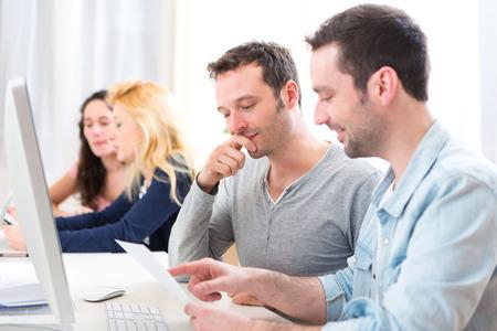 Vue de jeunes attrayants travailler ensemble au bureau