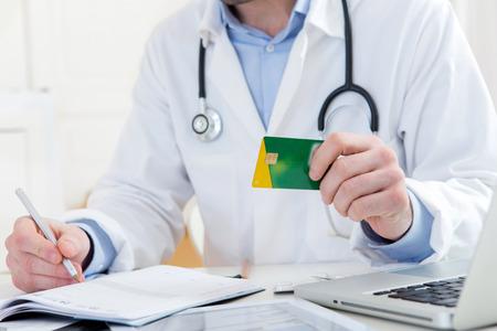 Weergave van een jonge aantrekkelijke arts die ziekteverzekeringskaart Stockfoto - 36325228
