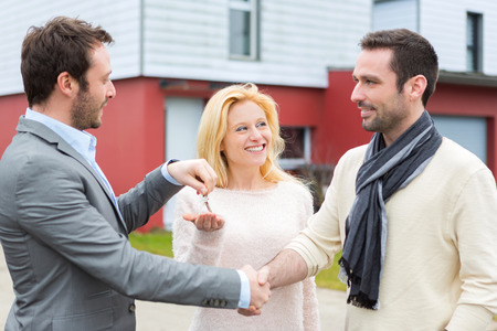 delivers: View of a Real estate agent delivers keys to young atractive couple