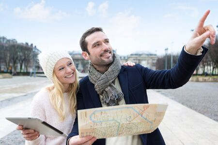 cheerfull: View of a Couple of young attractive tourists watching map