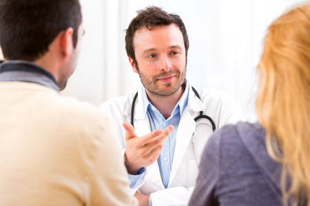 medecine: View of a Young attractive doctor advising a young couple of patients