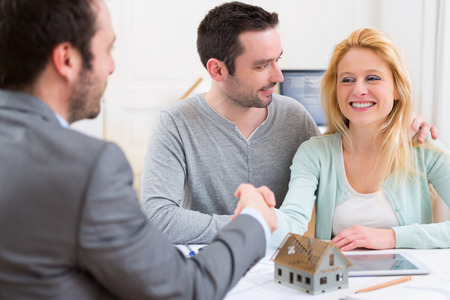 View of a Young happy couple handshaking real estate agent after signing contract Banco de Imagens