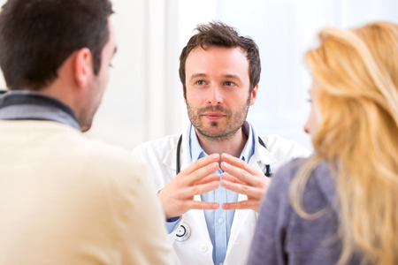 View of a Young attractive doctor advising a young couple of patients