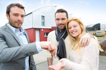 love strategy: View of a Real estate agent delivers keys to young atractive couple
