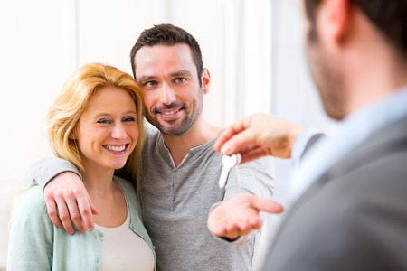 View of Real estate agent delivers keys of new house to young couple