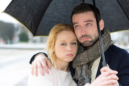 bored: View of a Portrait of a young couple on holidays under the rain Stock Photo