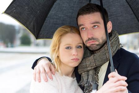 pareja enojada: Vista de un Retrato de una joven pareja en vacaciones bajo la lluvia