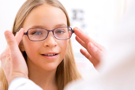 VIew of a Young little girl trying glasses at the optician Stock Photo
