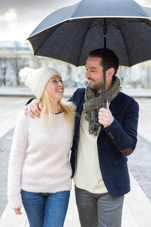 cheerfull: View of a Portrait of a young couple on holidays under the rain Stock Photo