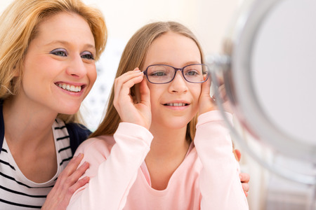 View of a Young little girl trying glasses at the optician w her mother Stockfoto