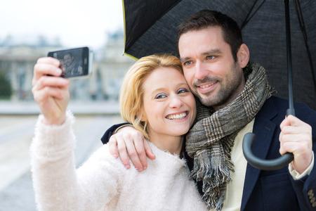 sotto la pioggia: Vista di una coppia giovane in vacanza sotto la pioggia presa selfie
