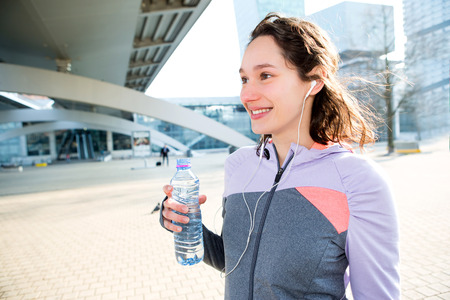 rehydration: View of a Woman drinking water during a running session
