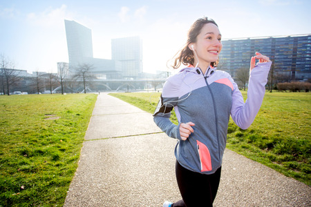 armband: View of a Young attractive woman running at the park Stock Photo