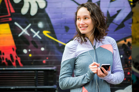 footing: View of a Young attractive woman adjust her music player before running