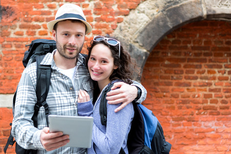 cheerfull: View of a Young couple of tourists using tablet to visit city Stock Photo