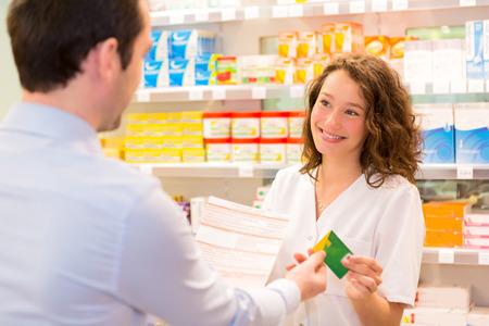 衛生の保険カードを取って、魅力的な薬剤師のビュー 写真素材