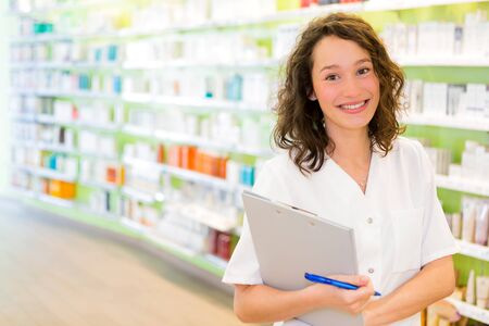 pharmacist: View of an Attractive pharmacist taking notes at work